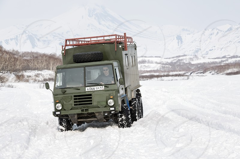KAMCHATKA PENINSULA RUSSIA - APRIL 4 2014: Old Swedish military off-road vehicle Volvo Laplander C304 (six-wheel drive) khaki color driving in snow along a country road on background volcanoes. photo