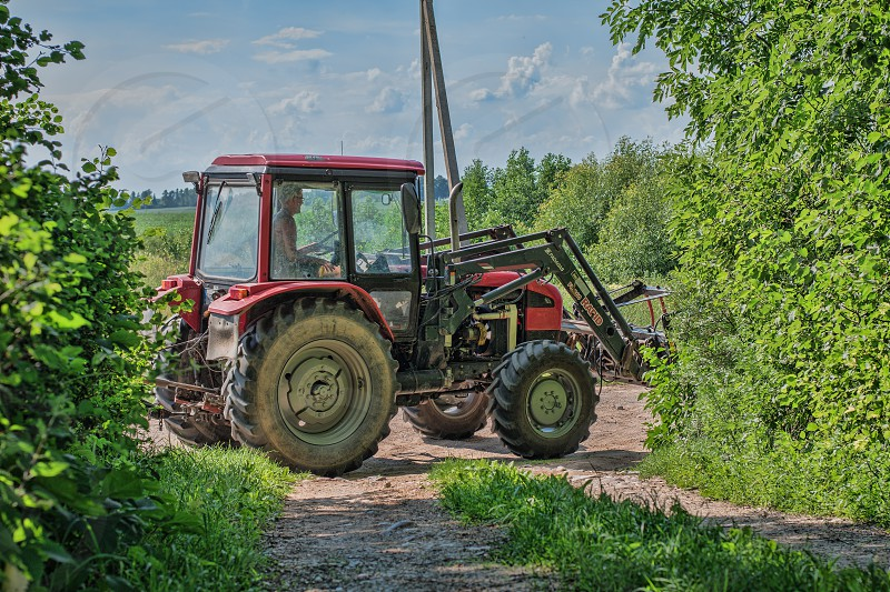 Tractor returning from the field in midday photo