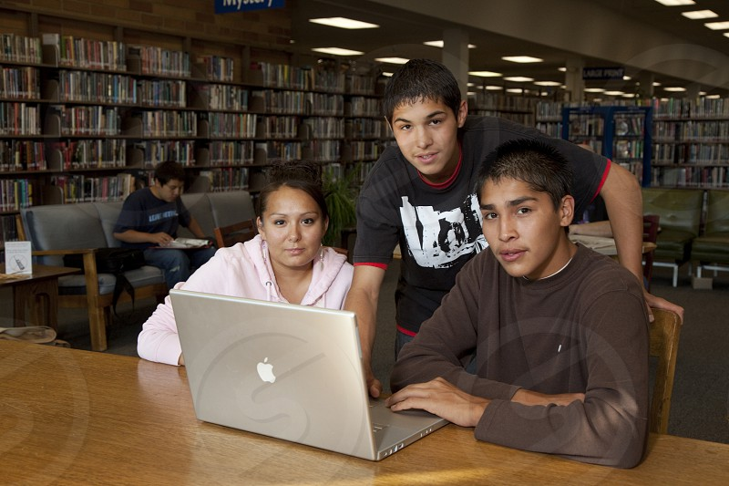 Three Native American teenagers inside a library study together using a laptop computer photo