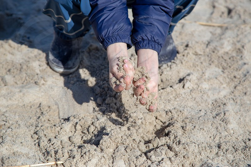a little boy digs with his hands in the sand photo