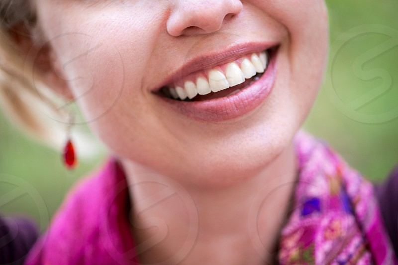 A beautiful young woman with long strawberry blond hair earrings and a colorful pink/magenta scarf smiling in front of a green outdoor natural background in the day.  photo