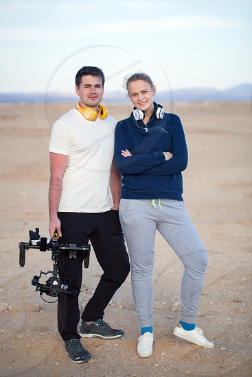 Young sport style man and woman with headphones on the beach. Videographer holding steadicam in hands photo