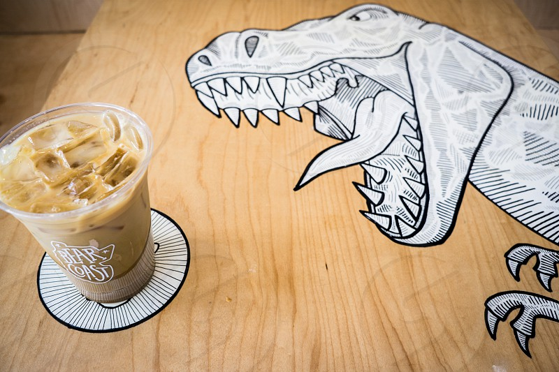 forced perspective photography of a dinosaur gaining the momentum of drinking the milkshake tea on brown wooden table photo