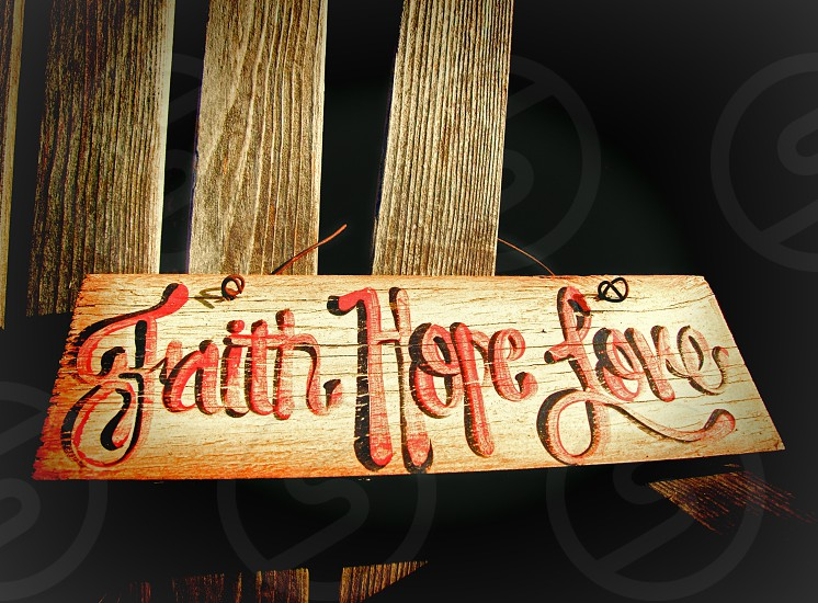 faith hope love wood sign hanging on a wood chair photo