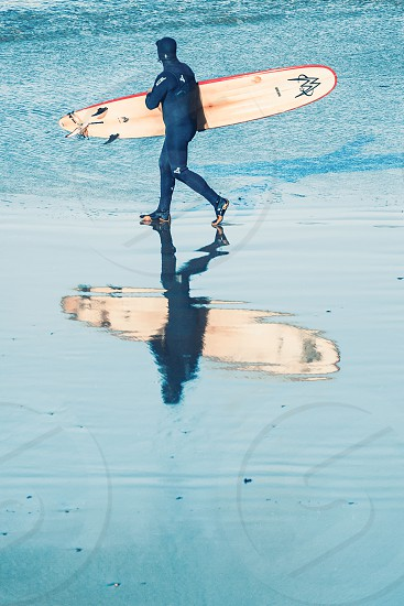 A surfer in wetsuit with his surf board under his arm walking towards the shore line photo