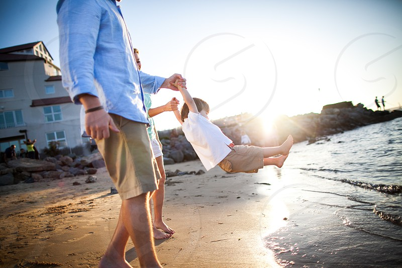 A couple kisses swings their young son baby kid boy by his arms over the water sea coast bay ocean waves with sunset sand bare feet sleeves shorts condo. photo