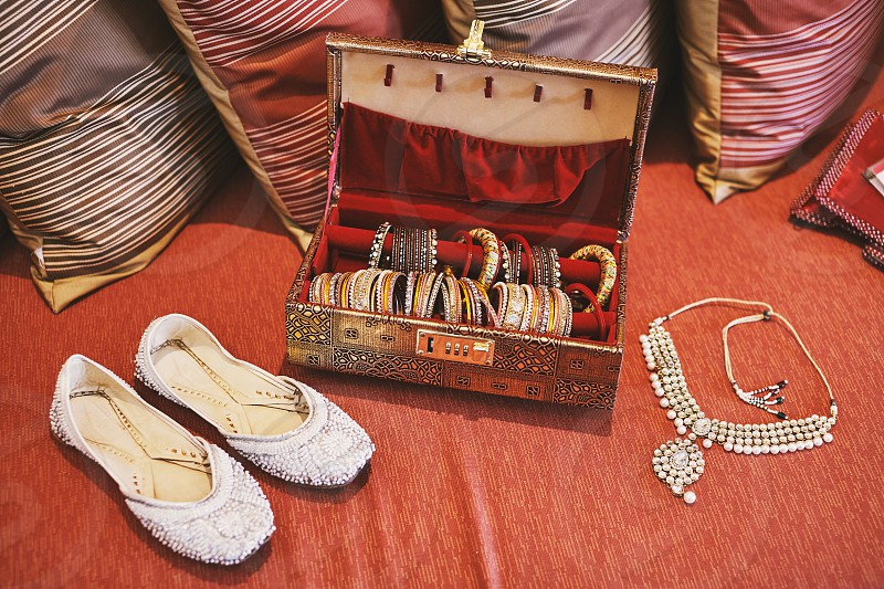 A collection of bangles or bracelets in the red velvet box and white glitter pump shoes and necklace of indian bride photo