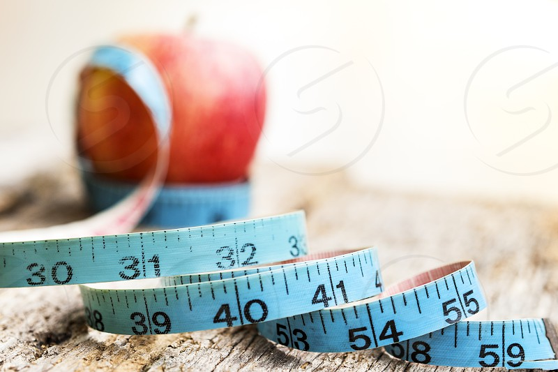 Close-up of measuring tape with red apple in the background on wooden table. Shallow depth of field. photo