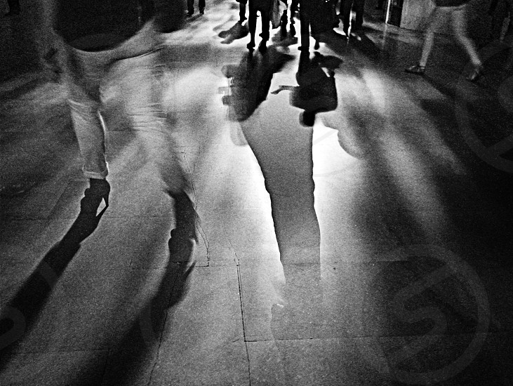 silhouette of person walking on walkway with tiled floor photo