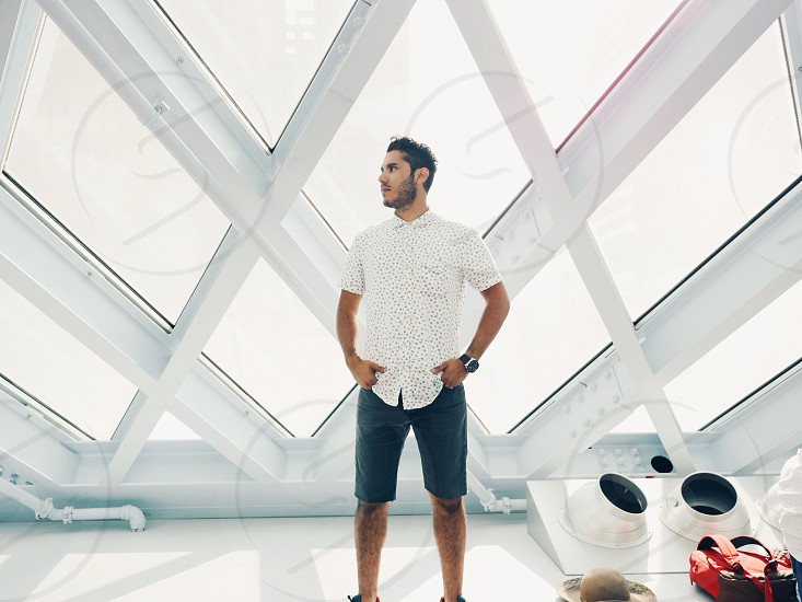 man in white dress shirt and shorts in white architectural lattice building photo