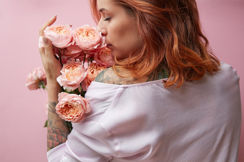 Young pretty woman with a tattoo sniffing a bouquet of pink roses media on a pink background View from the back. Mother's Day photo