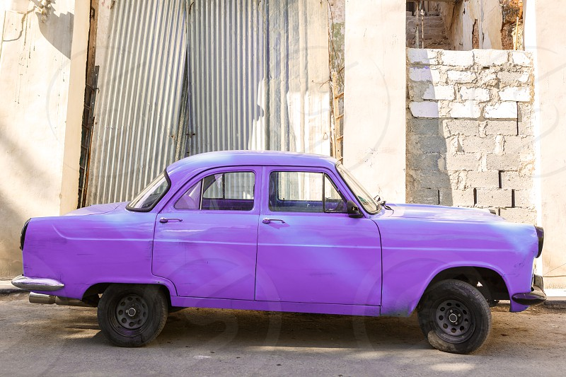 Old purple car parked on a street in Cuba photo