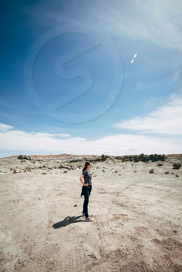 woman in black and white stripe blouse standing on dirt photo