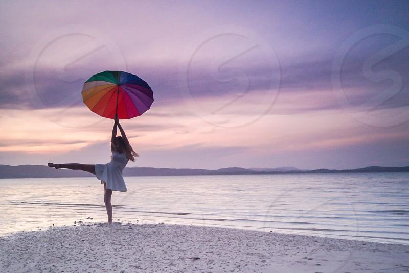 Balancing girl with colorful umbrella at lake sunset photo