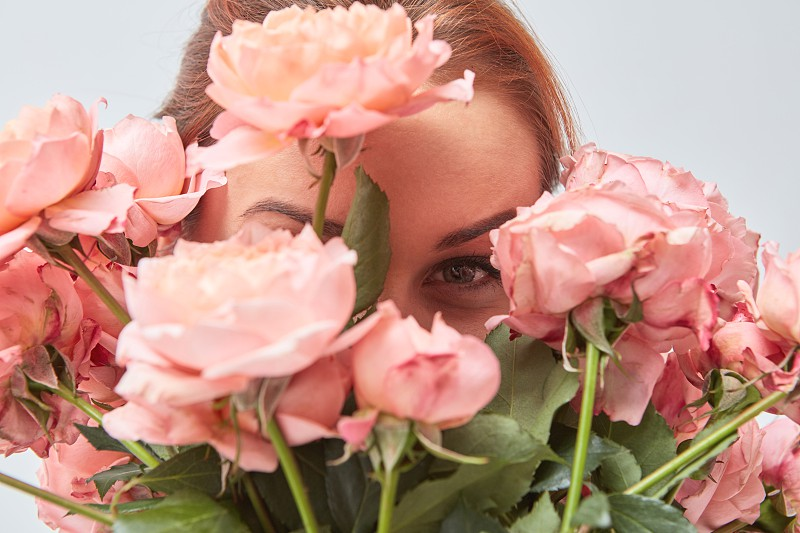 A smiling woman hides her face behind a bouquet of fragrant pink roses. St. Valentine's Day. Women's Day. Close-up photo