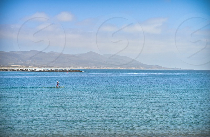 person doing paddle board on blue water during day photo