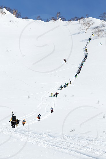 KAMCHATKA PENINSULA RUSSIA - MARCH 9 2014: Large group of sportsmens - skiers and snowboarders climbing the steep mountain for freeride. Competition Kamchatka Freeride Open Cup on Russian Far East. photo