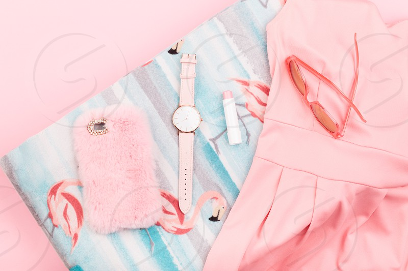 Female pink dress mobile phone in pink case watch with pink stripe on pink background photo