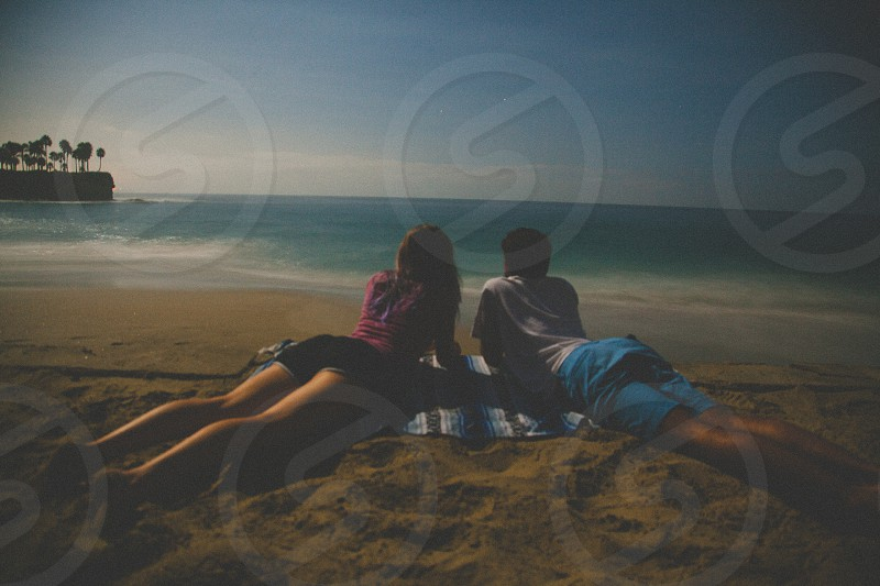 man and woman lying on brown sand during daytime photo