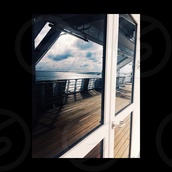A view of the ocean as seen reflected off of the glass door of a ship  photo