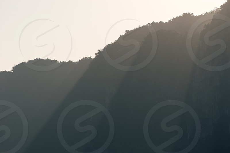Rays of sunlight fall through peaks of mountains silhouettes in morning haze photo