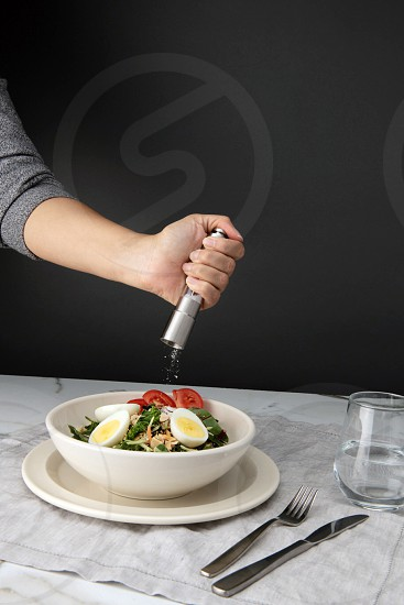 lifestyle food photography of a woman grinding salt on a cobb salad photo