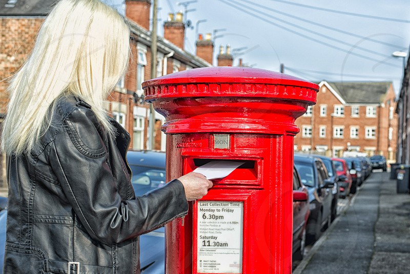 woman putting the envelope on mail box photo