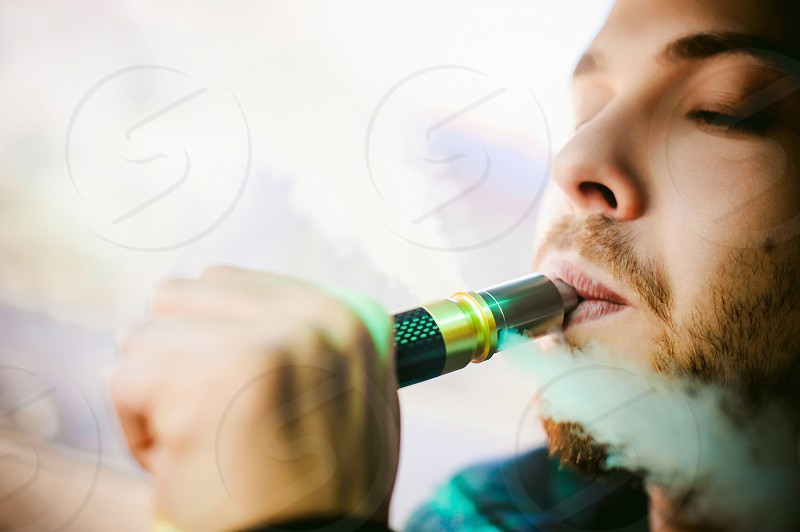 young vaper man with beard vaping mechanical mod. Guy smokes an electronic cigarette by blowing a smoke vapor. Bringing rda mouthpiece to the lips on colorful background photo