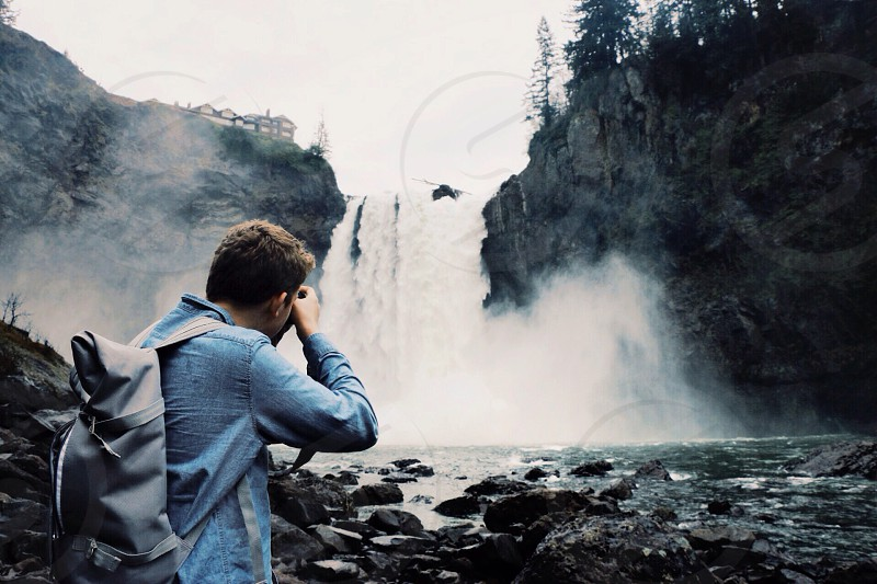 view of a man in a blue long sleeved shirt taking a photo of the waterfalls photo