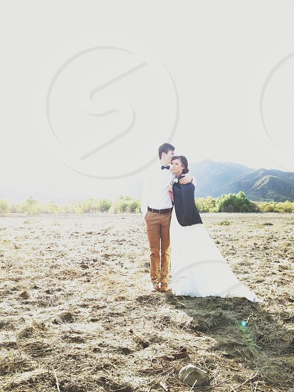 standing brunet man and woman wearing formal clothes on sandy beach photo
