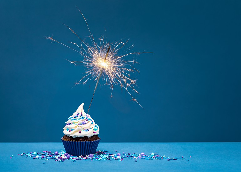 Birthday Cupcake with sparkler against a blue background. photo