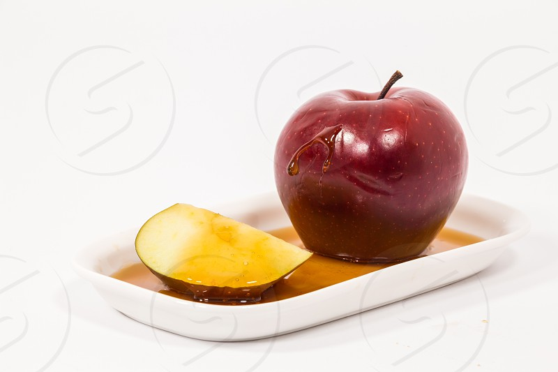 Red apple and red apple slice with drops of honey on white plate with honey isolated on a white background. Symbols of Jewish New Year - Rosh Hashanah.   photo