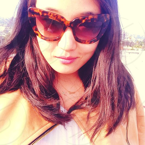 woman wearing brown frame sunglasses smiling photo