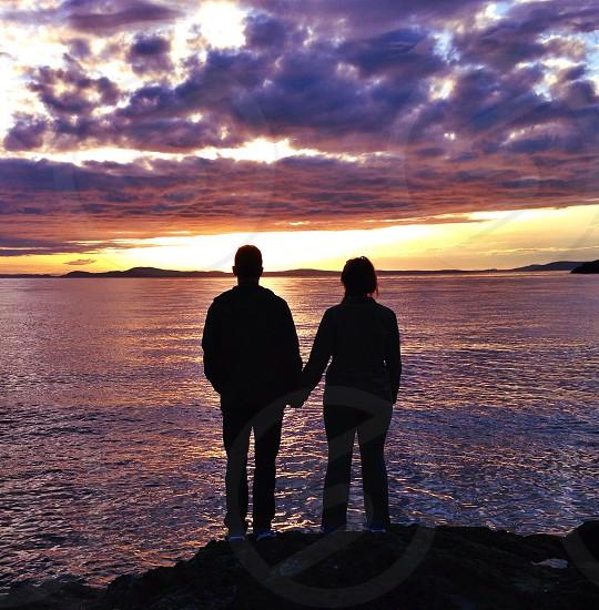 man and woman watching sunset photo