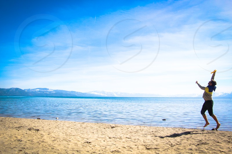 man jumping on seashore beside rippling ocean under blue cloudy sky during daytime photo