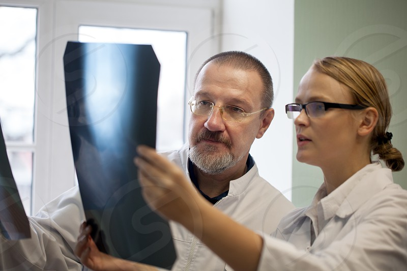 Young and experienced doctors looking at two x-ray images and trying to make a right diagnosis photo