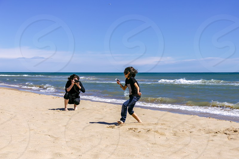 Professional photographer with a camera shoots a running teenager on a sandy beach of the ocean coast on a sunny spring day photo