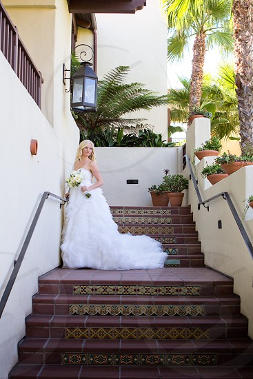 woman wearing white bridal dress standing on maroon and brown steps near white and brown building photo