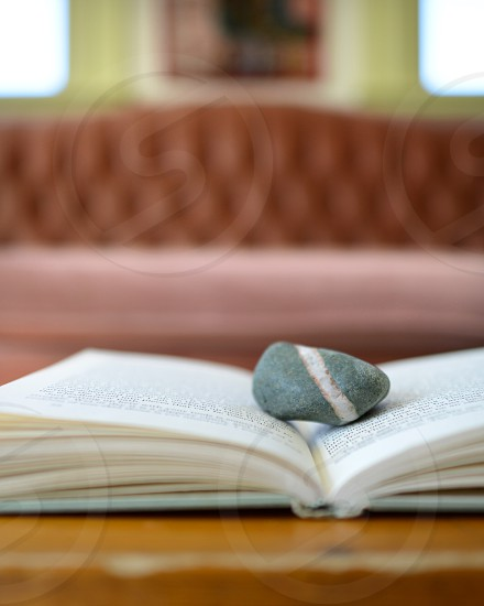An open book with a striped rock on it. photo