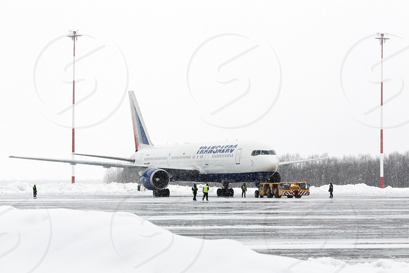 PETROPAVLOVSK-KAMCHATSKY KAMCHATKA RUSSIA - MARCH 19 2015: Airdrome trucks pulling airplane Boeing-767 Transaero Airlines at airport of Petropavlovsk-Kamchatsky (Elizovo airport) during a snowfall and poor visibility. photo
