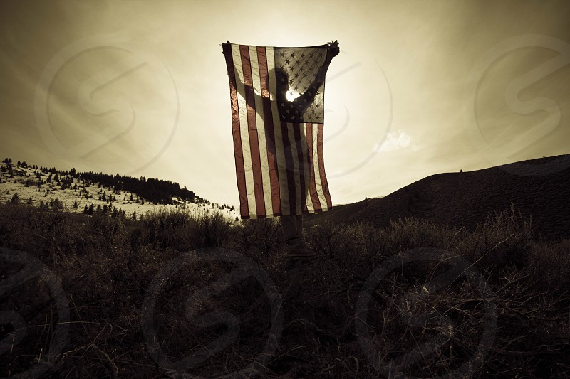 person holding us flag grayscale photography photo