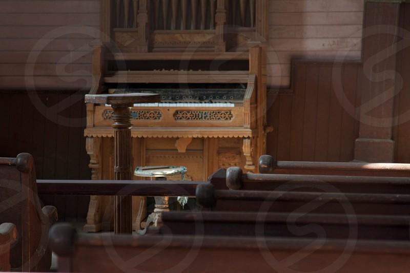 brown upright piano in front of brown wooden chairs photo