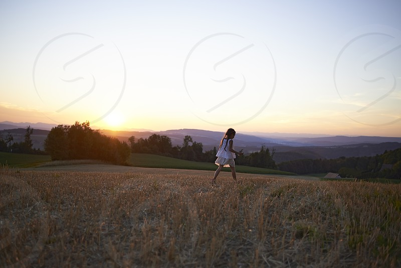 Beautiful landscape of a hill in the Swiss Alpes with a young girl in a white dress walking down photo