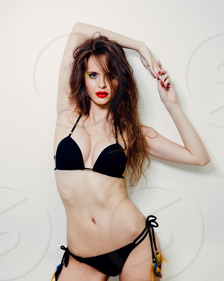 woman in black string bikini standing against white painted wall photo