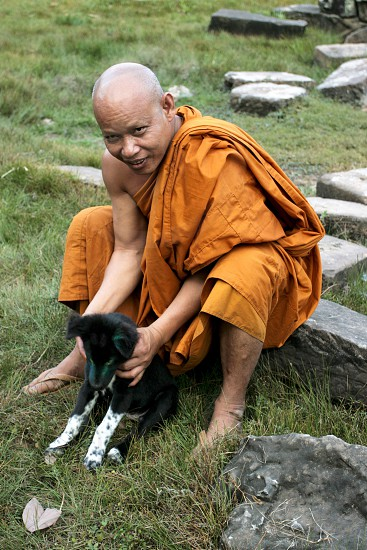 Buddhist monk playing with his dog on the grounds of Bayon Angkor Thom. photo