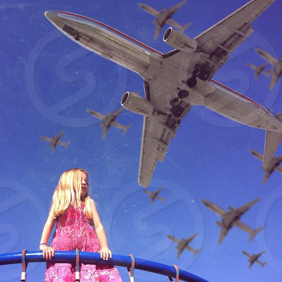 white jet planes over a girl in pink dress photo