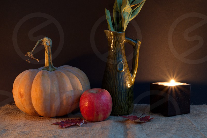 Halloween decoration with pumpkin apple leaves and candle against the dark background photo