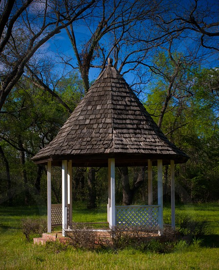 brown and white gazebo on grass field photo