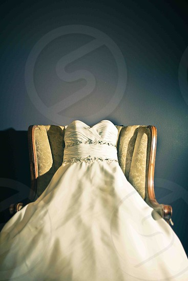 white long gown on brown cushioned wooden framed armchair photo