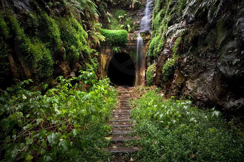 A waterfall drapes over a hidden tunnel near Sydney New South Wales Australia. photo